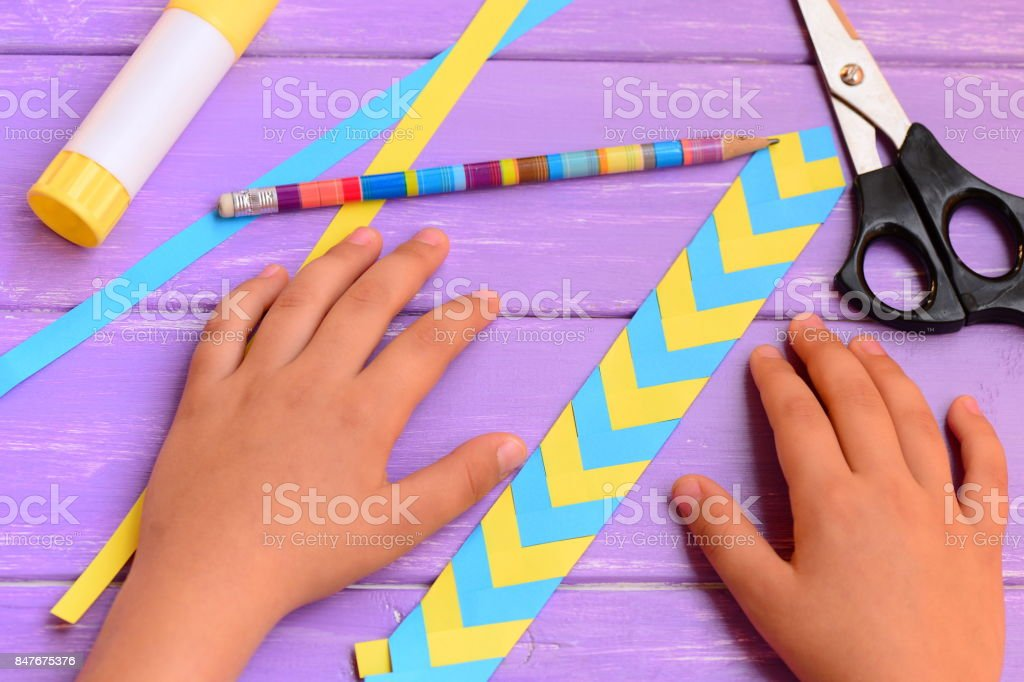 Child made a bookmark from yellow and blue folded paper. Child shows a paper colored bookmark. Stationery on a bright wooden table. Children workplace in school or at home stock photo