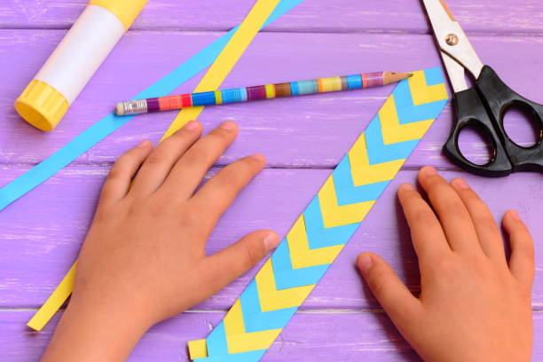 子は、黄色と青の折り畳まれた紙からブックマークをしました。子どもは、紙着色されたブックマークを示しています。明るい木製のテーブルのひな形です。学校や家庭で子どもたちの職場 - 栞 ストックフォトと画像