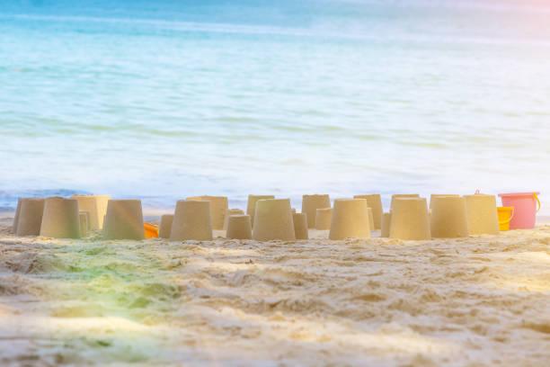 kind machte viele kegelfiguren aus strandsand. sonniger tag und blaues wasser des meeres auf einem hintergrund. sommerurlaub der kinder - sandmann stock-fotos und bilder