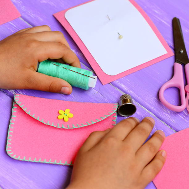 child made a simple felt purse. handicraft supplies on a wooden table. fun and easy teaching kids to hand sew. kids sewing concept - kids holding hands zdjęcia i obrazy z banku zdjęć