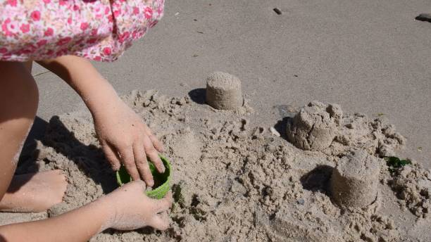 Child make sandcastle with sand mold tool on beach stock photo