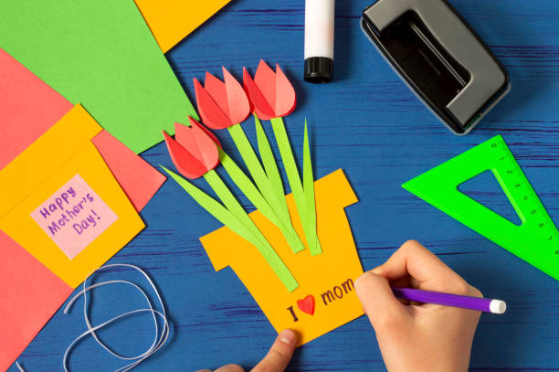 Child makes card for Mother's Day. Step 10 stock photo