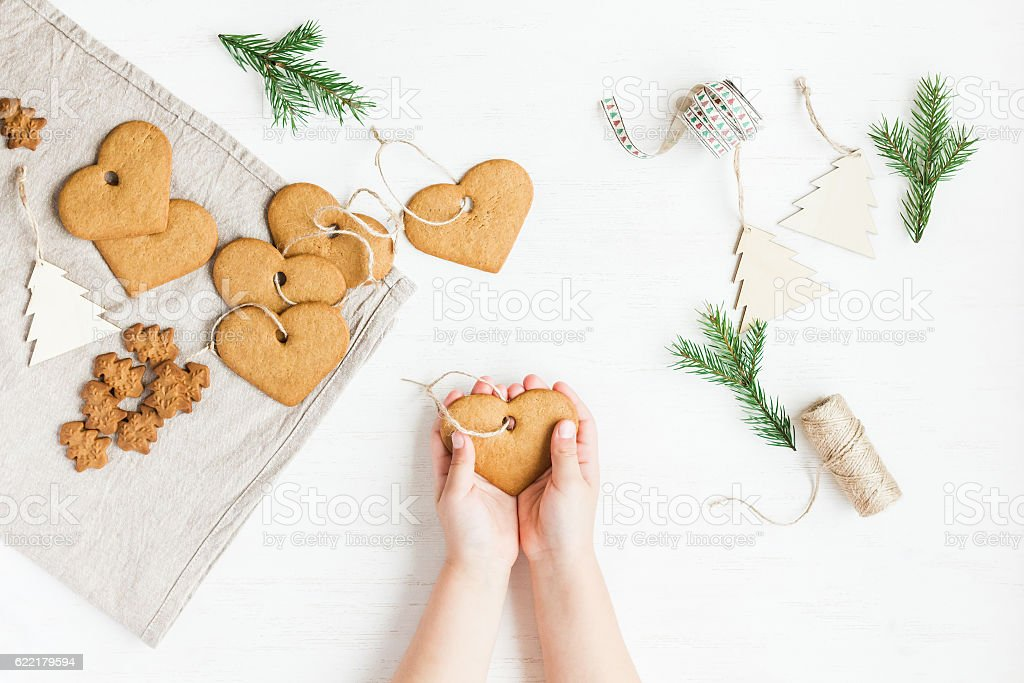 Child making christmas decorations from cookies. flat lay, top view stock photo