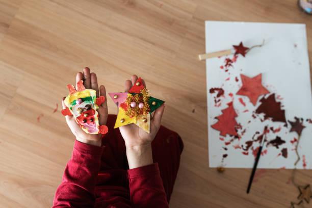 Child making christmas ornaments stock photo