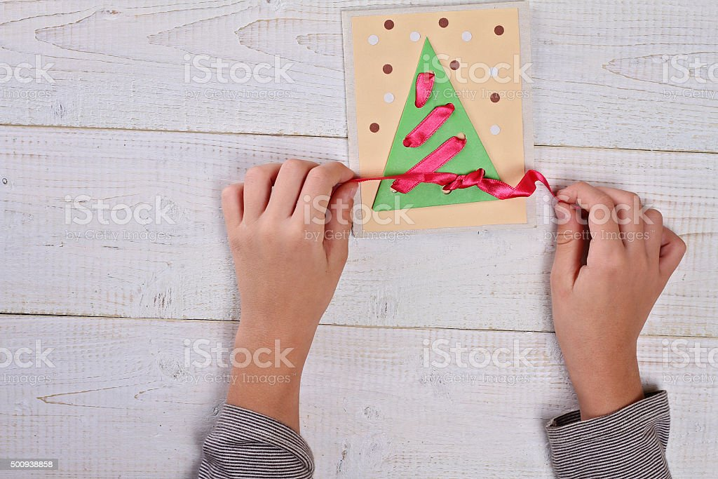 Child   making Christmas Tree from colored paper. stock photo