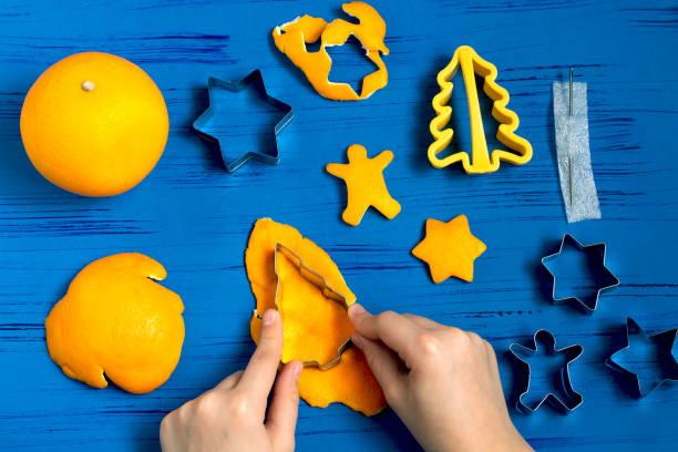Child making decorations of orange peel for Christmas. Step 2 stock photo