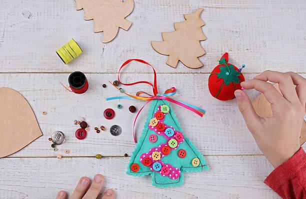 child making felt christmas tree decoration ornament close up - filzunterlage stock-fotos und bilder