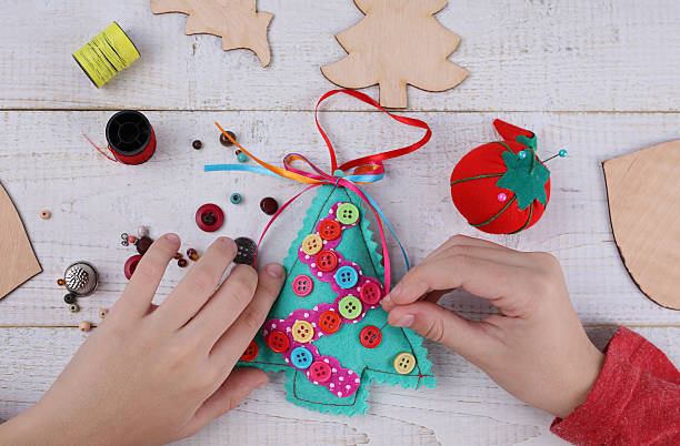 child making felt christmas tree decoration ornament - filzen kinder stock-fotos und bilder