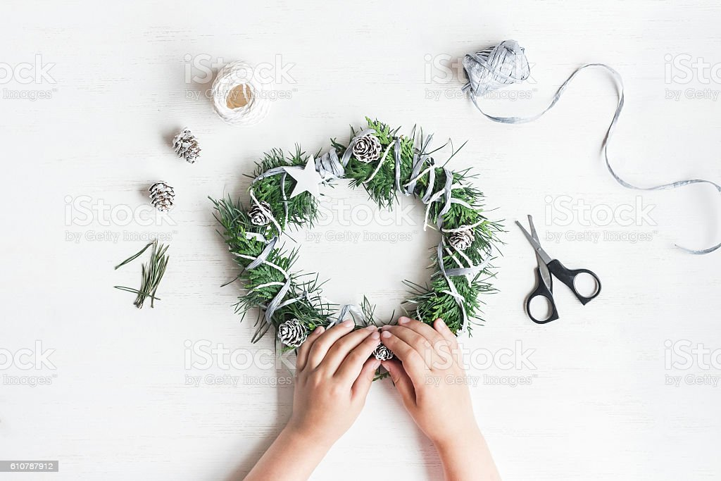 Child making handmade christmas wreath. Top view, flat lay – Foto