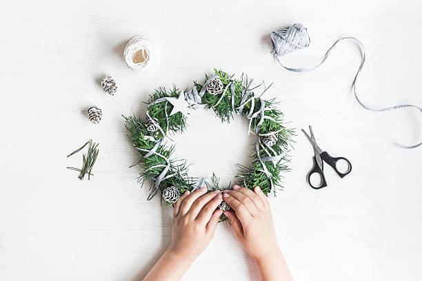 child making handmade christmas wreath. top view, flat lay - diy xmas stock-fotos und bilder