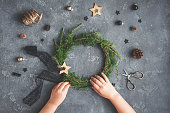Christmas composition. Child making handmade christmas wreath on dark table. Top view, flat lay