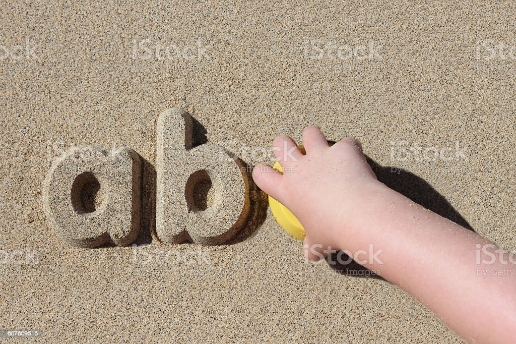 Child making sand letters on the beach - foto de stock