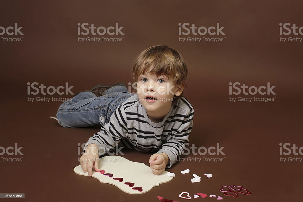 Child making Valentine's Day Craft with Hearts stock photo