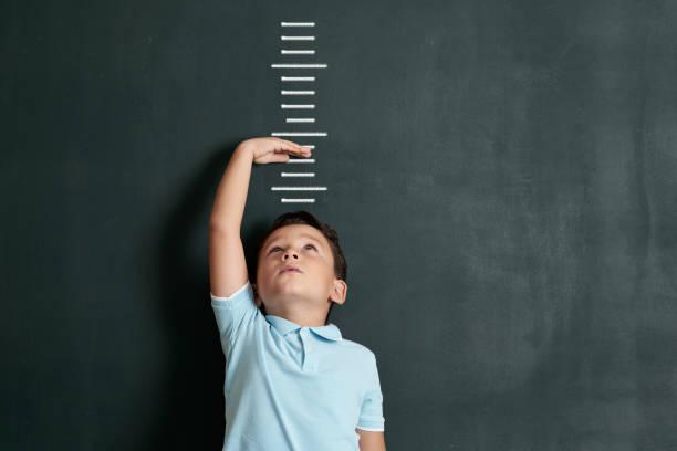 孩子在牆上測量他的身高。他成長得太快了。 - 測量 個照片及圖片檔