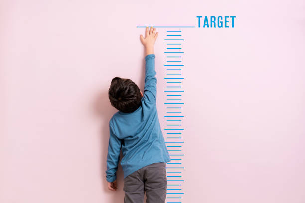 Child measuring his height stock photo