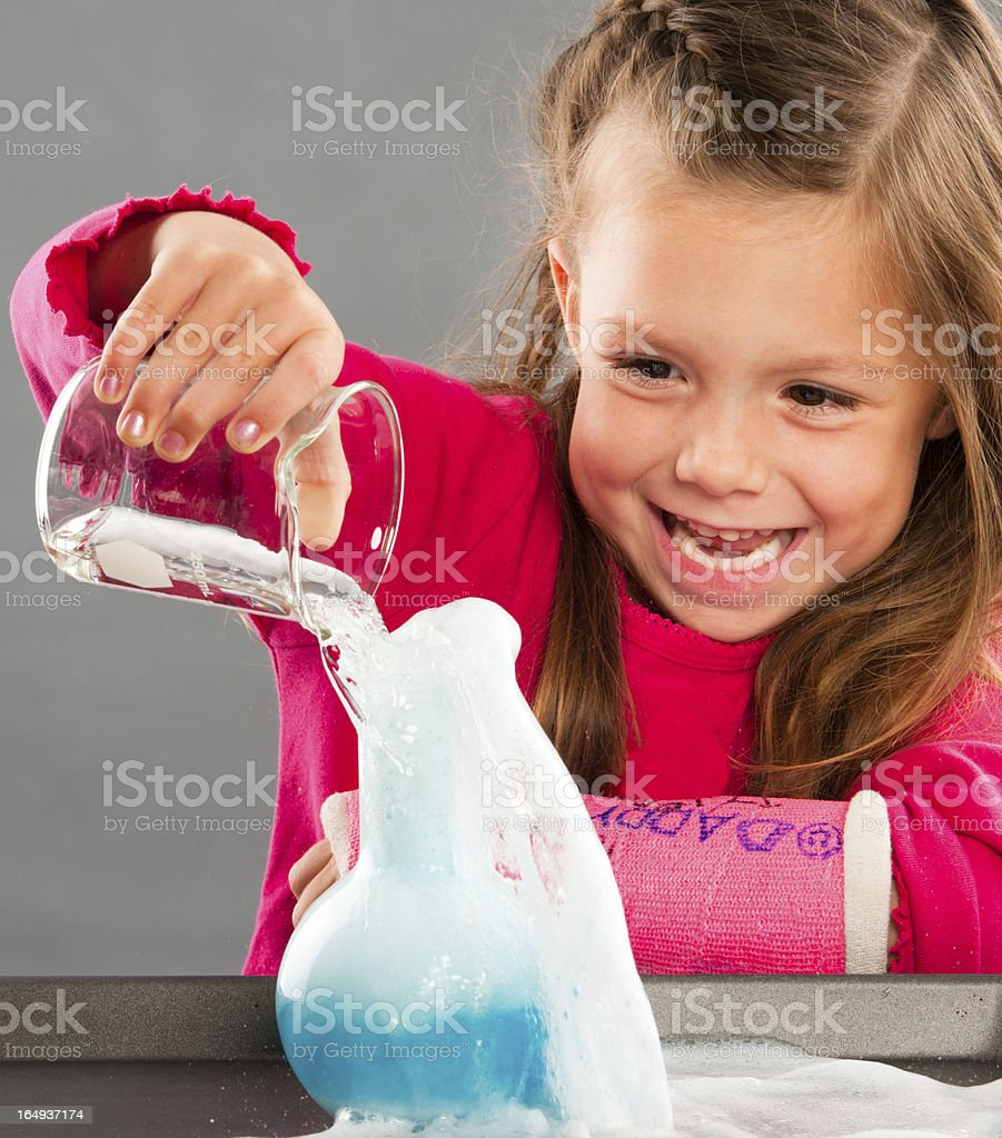 Child mixing two liquids during science experiment stock photo