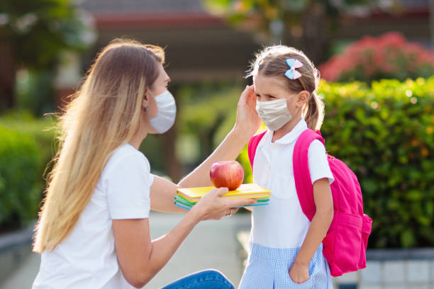Child, mother wearing face mask going to school. stock photo