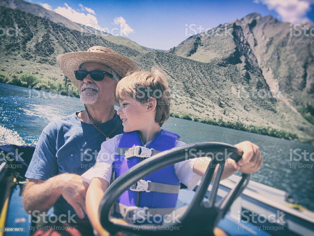 Child Mountain lake boating with Grandpa stock photo