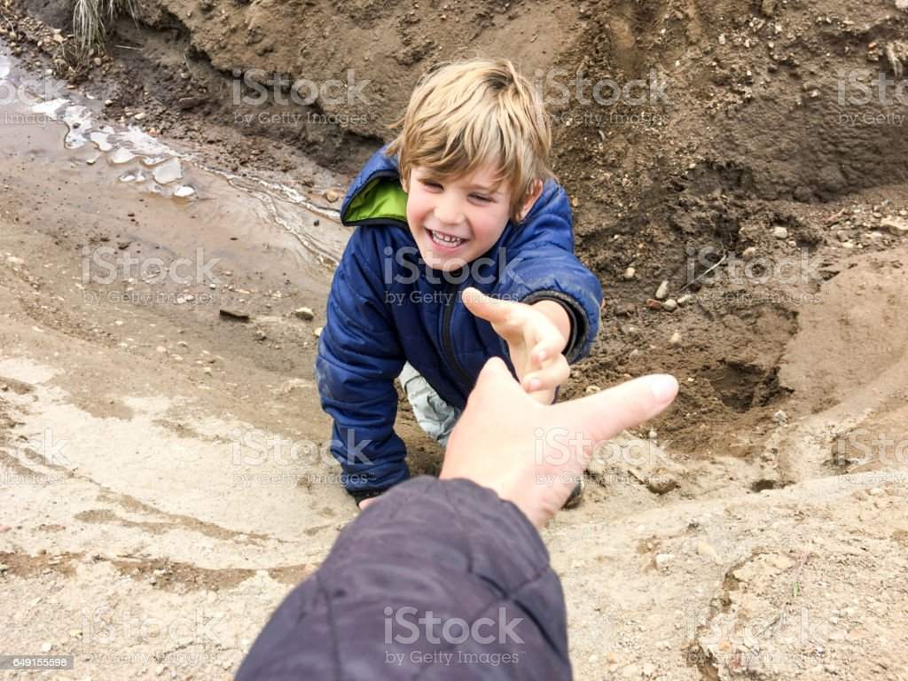 Child needing help out of ditch stock photo