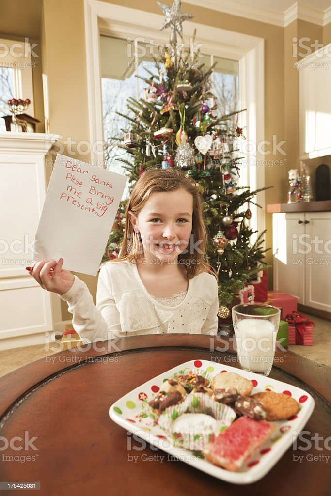 Young child, a girl with santa\'s milk and cookies, writing a...