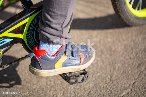 istock child on a bicycle at asphalt road. Bike in the park moving 1139265307