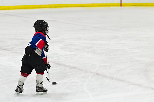 Child on a breakaway during ice hockey game stock photo