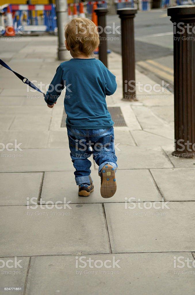 Kind auf einer Leine zu Fuß in Gehweg – Foto