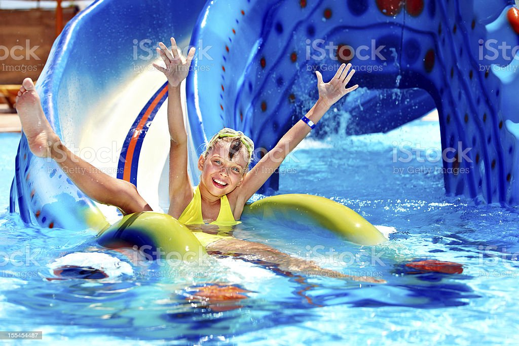 A child on a water slide at aqua park stock photo
