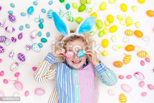 istock Child on Easter egg hunt. Pastel rainbow eggs. 649569204