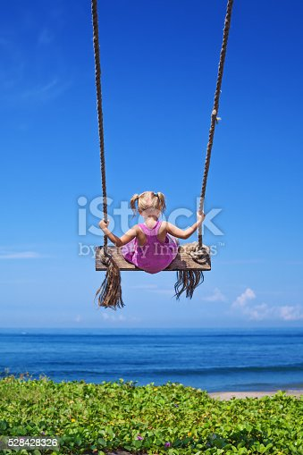 istock Child on flying high on rope swing on sea beach 528428326