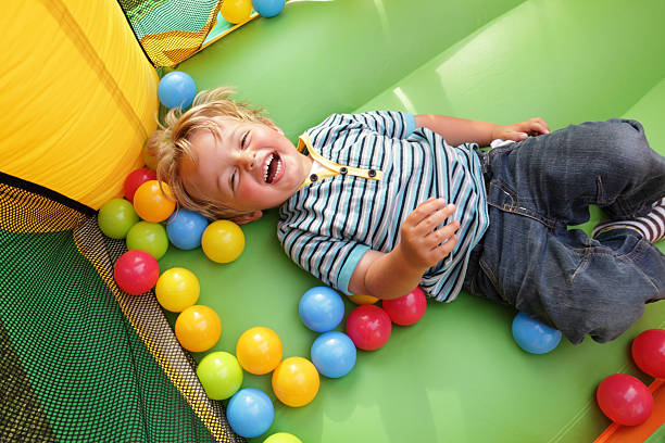 Child on inflatable bouncy castle 2 year old boy smiling on an inflatable bouncy castle preschool student stock pictures, royalty-free photos & images