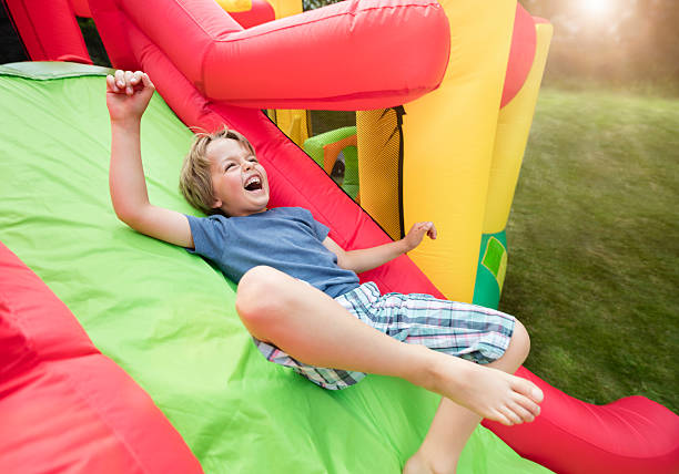 Child on inflatable bouncy castle slide Boy jumping down the slide on an inflatable bouncy castle carnival children stock pictures, royalty-free photos & images