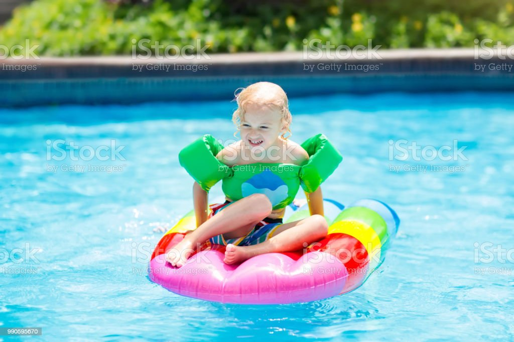 Child on inflatable float in swimming pool. stock photo