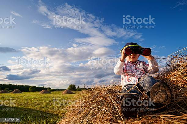 Photo of Child on mounds of hay with binoculars