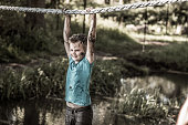 Individual child having sporty fun at a public mud run obstacle course