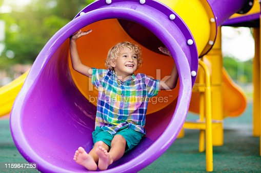 Child playing on outdoor playground. Kids play on school or kindergarten yard. Active kid on colorful slide and swing. Healthy summer activity for children. Little boy climbing outdoors.