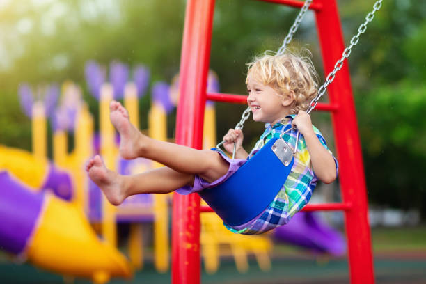 Child on playground. swing Kids play outdoor. stock photo