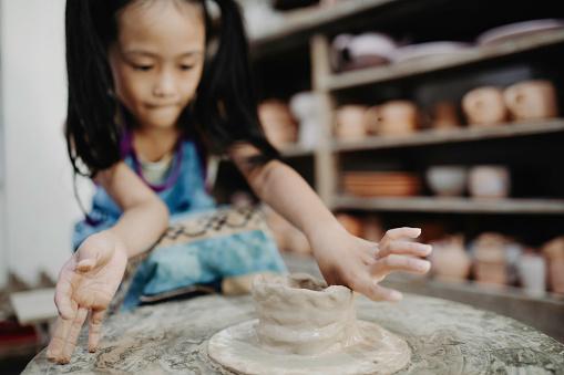 child on pottery art class playing