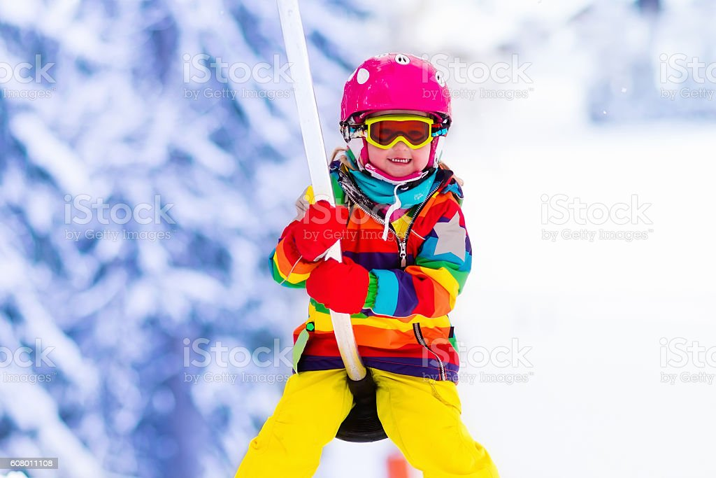 Child on ski lift going uphill in the mountains stock photo