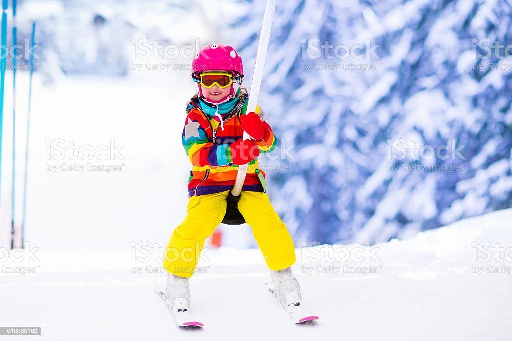 Child on ski lift in alpine resort stock photo