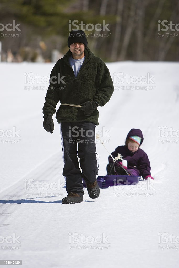 Child on sled pulled by dad on a snowy surface royalty-free stock photo