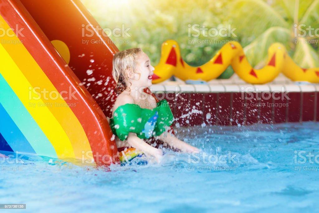 Child on swimming pool slide. Kids swim. Water fun stock photo