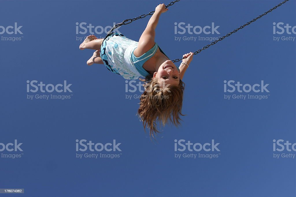 Child on Swing A little girl is swinging high against a blue sky. Low angle view. Plenty of copy space. Above Stock Photo