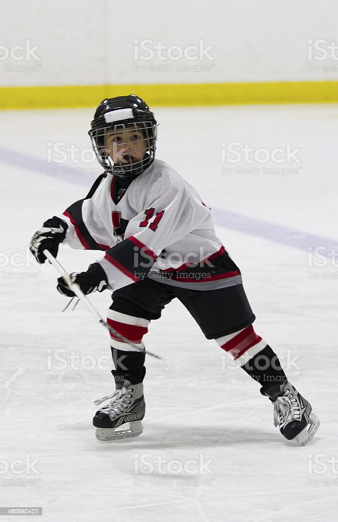 A child on the ice in his hockey uniform stock photo
