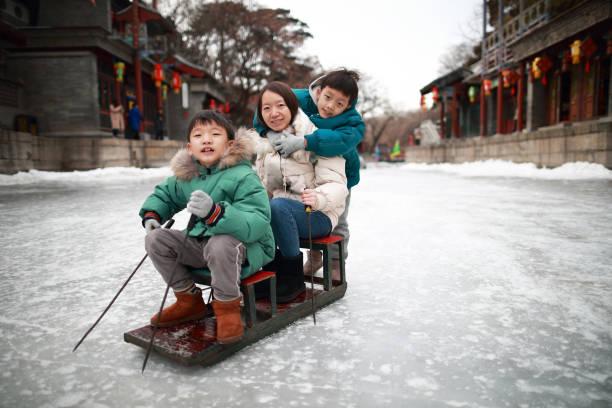 Kind auf dem See friert, um Rodeln, Schlittschuhlaufen, Eisrad im Sommerpalast in Peking im Winter zu genießen, – Foto