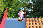 A young child girl enjoys a day at the playground toboggan
