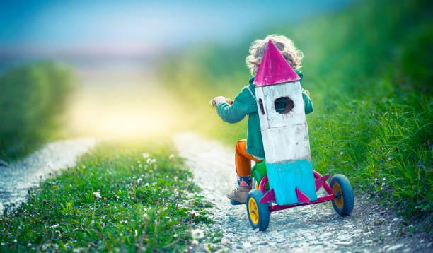 kind auf dem dreirad tragen eine weltraumrakete spielzeug - fahrradträger stock-fotos und bilder