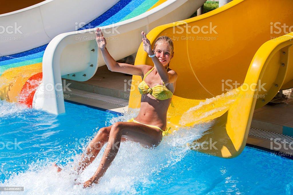 Child on water slide at aquapark jump . stock photo