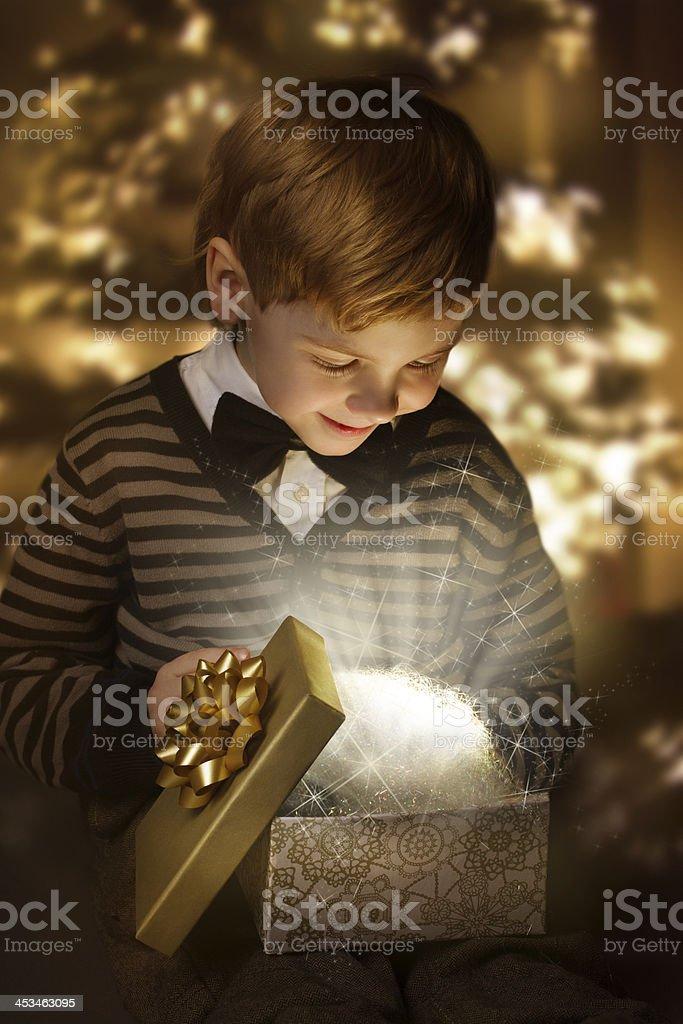 Child opening birthday present box. Magic shining gift. stock photo