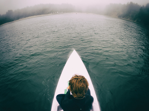 Child paddle boarding on a cold, foggy ocean in Oregon